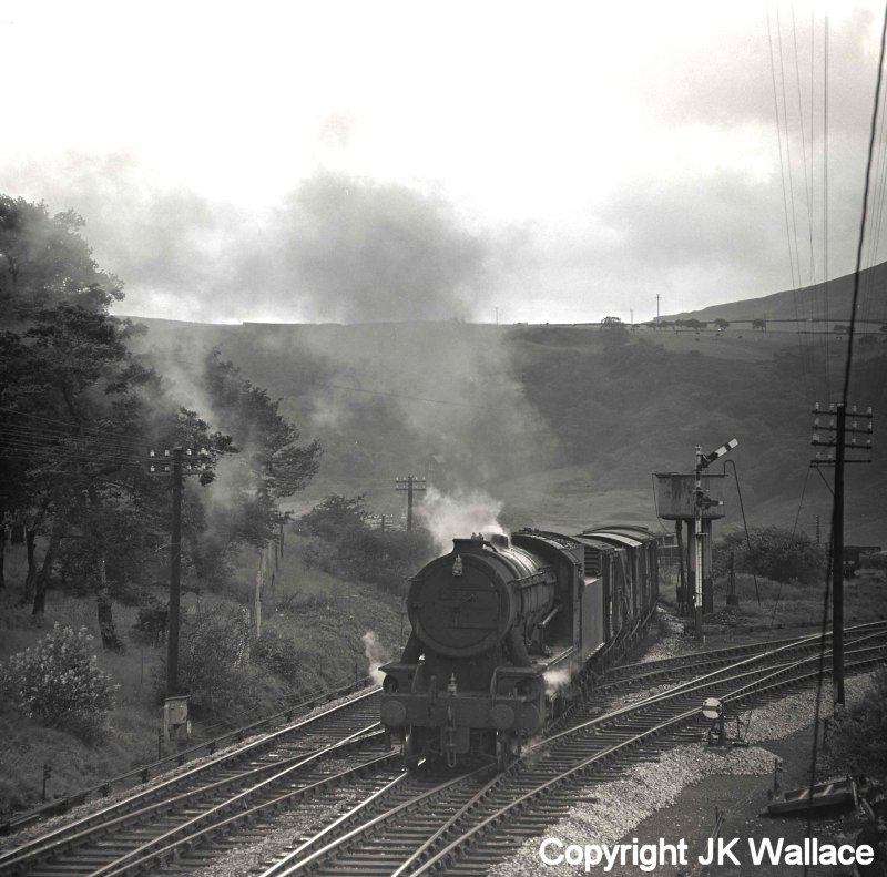 Eric F Bentley caught WD Austerity 2-8-0 90345 at Stansfield Hall (Todmorden) on a westbound mixed freight stopping passing the water tank, and about  to cross the junction before picking-up a banking loco on Saturday 30 July 1966