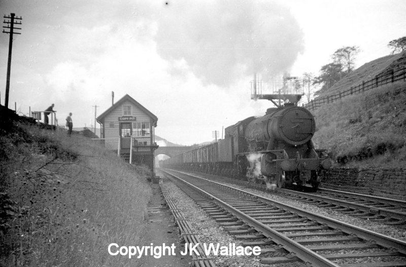 WD Austerity 2-8-0 90412 arrives at Copy Pit, having completed the climb up the Cliviger George from Stansfield Hall Junction in Todmorden some time in the early 1960s. Banker Crab 2-6-0 42727 can be seen under the road bridge still under steam. The train is bound for Rose Grove.