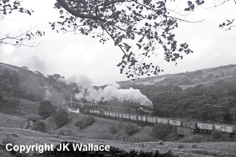 WD 90658 heads towards the entrance to Holme Tunnel and Rose Grove with a loaded coal train whilst the 13:30 Blackpool Central - Wakefield Kirkgate hauled by an unidentified Black 5.