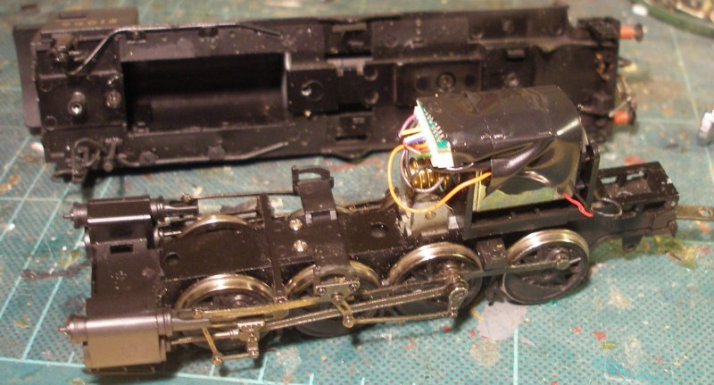 Bachmann WD 2-8-0 with body removed, and the original Lenz 1025 hard wired and taped in position above the motor.