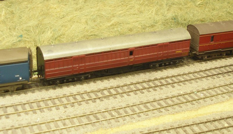 A 4mm scale LNER Diagram 129 non-vestibuled bogie van E70253E in early BR crimson livery, with slight weathering. It has white metal GER 8' bogies with pin-point axles in cups. It is fitted with Jackson screw couplings, although the buffers are solid (not sprung). Bought from the long-closed model shop in Charlotte Place off Mortimer Street, London in the 1980s. The prototype was based on the design of the standard GNR milk van and used the underframe specified for non-vestibuled carriages. The bodies of the vans, 51 feet 1.5 inches by 9 feet, had two sets of double doors to each side. All except one of these vans were allocated to the GE section. Those built 1926/7 were built with dual brakes.