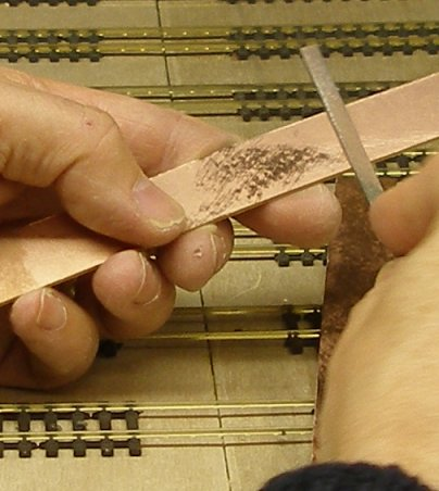The strip is roughened with a file to ensure a good purchase by the solder.