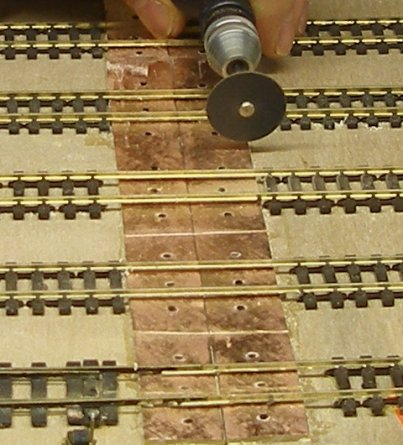The copperclad is cut through between each rail, both between the two rails of each track, and the strip in between tracks to prevent short circuits.