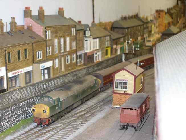Bachmann Class 40 passes a row of shops based on a prototype in Burnley Row, Todmorden.