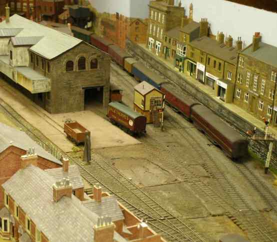 Parcels Train passes a model of Haworth Goods Shed; shops in Burnley Road Todmorden to the right.