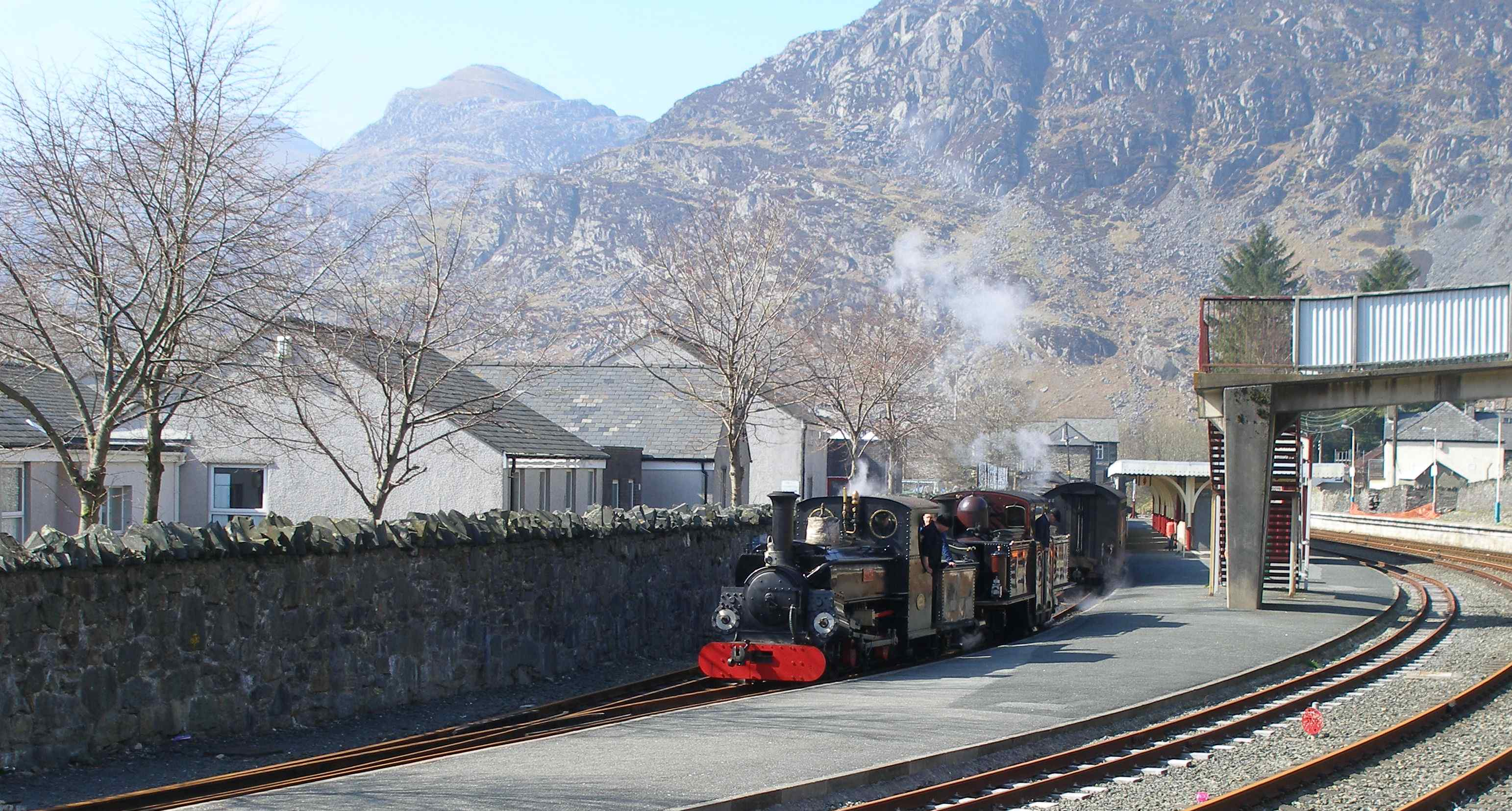 'Merddin Emrys' and 'Linda' running round at Blaenau Ffestiniog. The Network Rail standard gauge line in the foreground once ran through to Bala and Bala Junction; latterly servicing the power station at Trawsfynydd, and now terminates at a buffer stop to form a headshunt. Track remains to the Power Station, and has recently been cleared by local volunteers as part of a rail cycle tourist attraction proposal, although the infrastructure would require a major maintenance effort for trains to be restored.