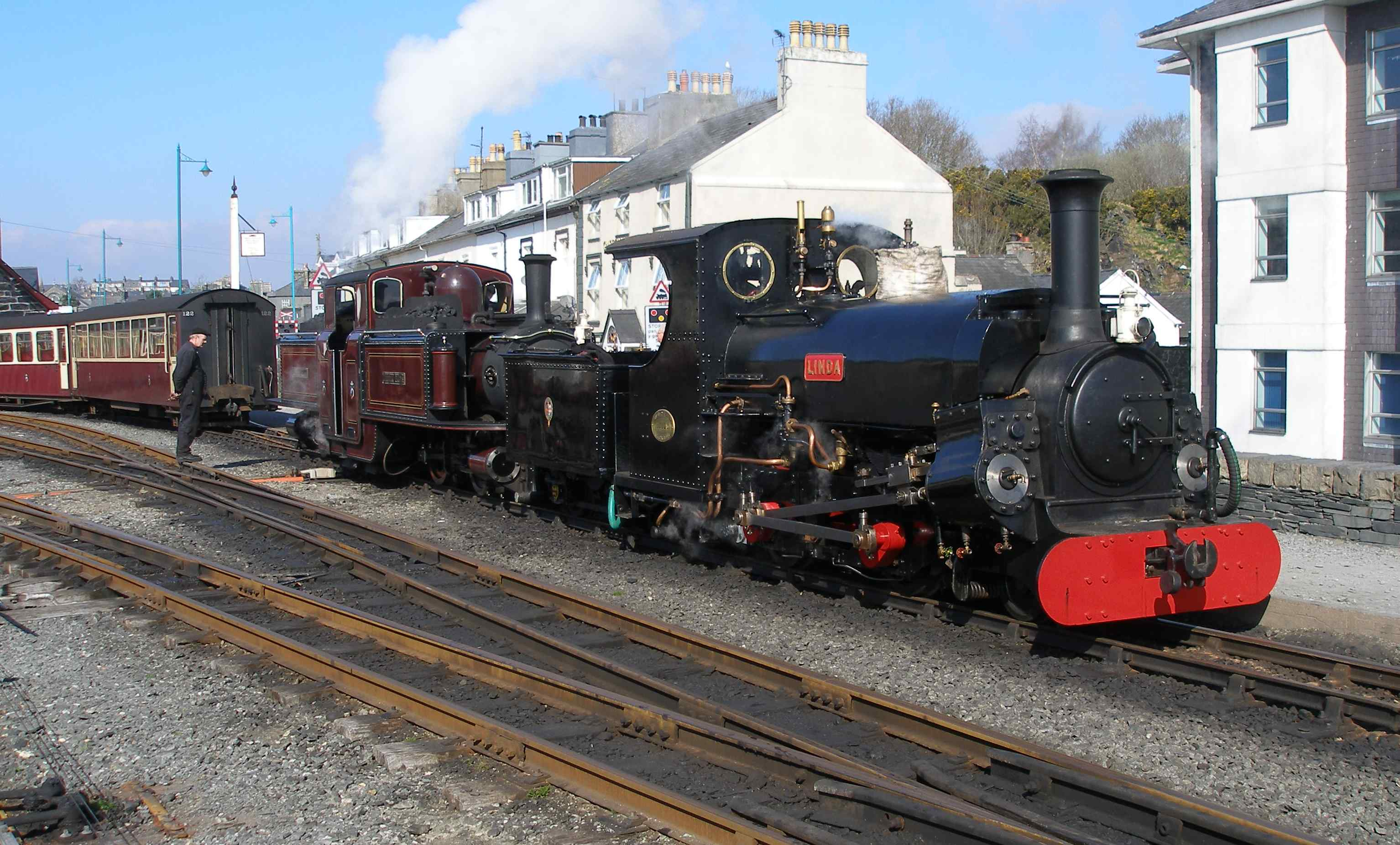 'Linda' and 'Merddin Emrys' make a fine sight as they back down on to their train at Porthmadog Harbour Station. This area here is now being redeveloped to create a new platform for Welsh Highland Railway trains to be terminated. This has involved widening the embankment and relocating the wave wall constructed in 1940. The new signal box and relay room are now located behind and to the left of the photographer. The new scheme will feature lower quadrant semaphore signals and the restoration of a 'trident' - the original was brought down from Blaenau in 1923 but was finally blown down in the late 1960s.