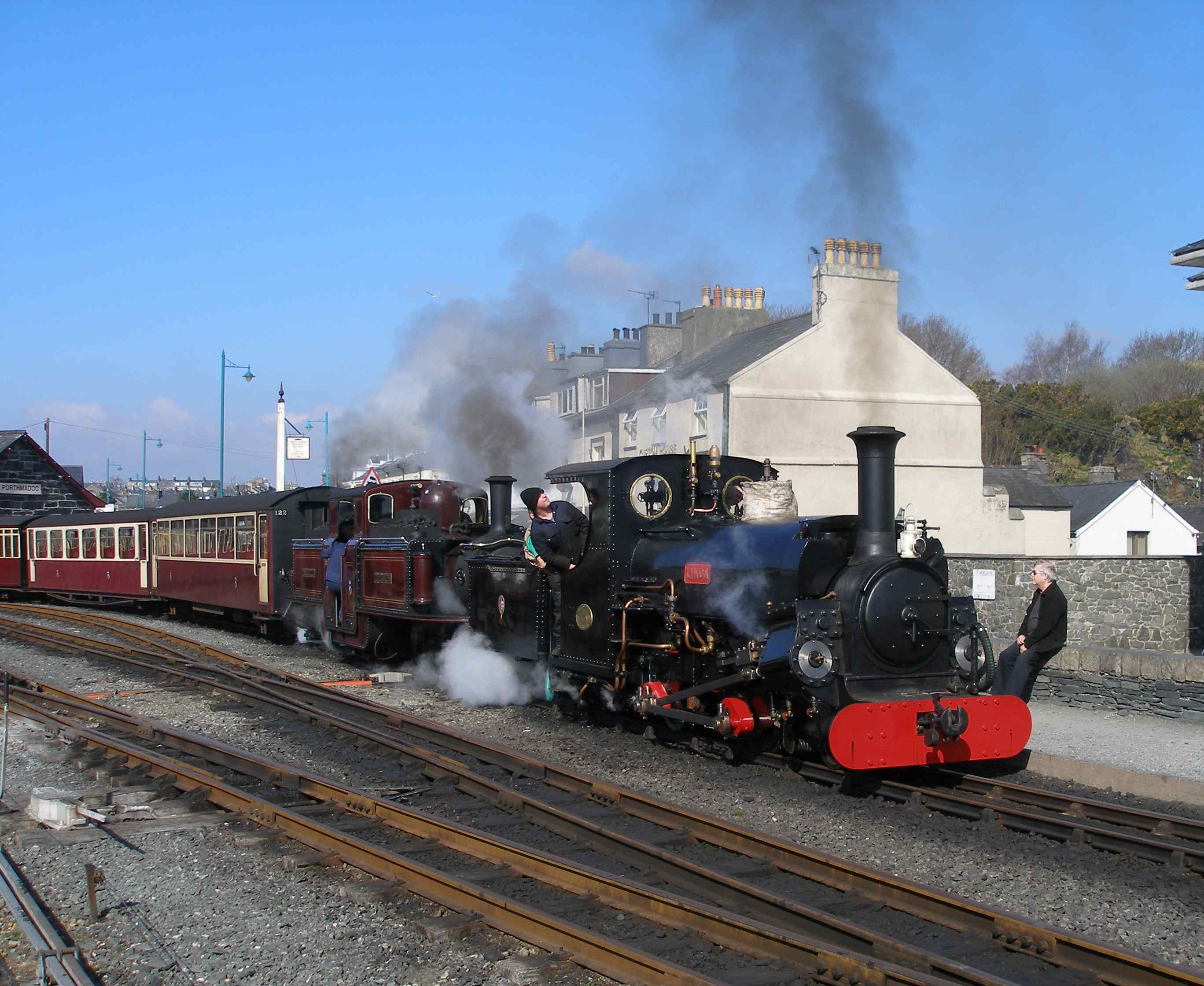 'Linda' and 'Merddin Emrys' set off with the empty coaching stock (ecs) for Blaenau Ffestiniog. Both locos were converted to oil firing in the 1970s. This was undertaken as the railway's medium-sized locos had smaller grate areas that reflected their industrial origins ('Linda' and 'Blanche') and therefore were more prone to fire-throwing when worked hard - which was virtually all the time! 'Merddin Emrys' had a better ratio of grate to traffic effort and arguably was less prone to fire throwing and might have been better kept as a coal burner. It's conversion to coal required major work on its tanks, which at the time were virtually brand new. A second set of traditionally-styled tanks were made at the same time for 'Earl of Merioneth' but these have not yet been fitted, and these to will have to be modified for coal.