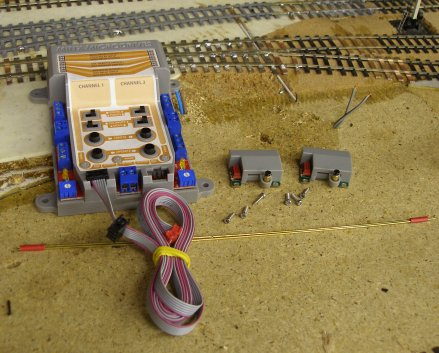 The Minx point and signal actuator kit laid out to show control unit, ribbon cables, control rods, actuators and screws