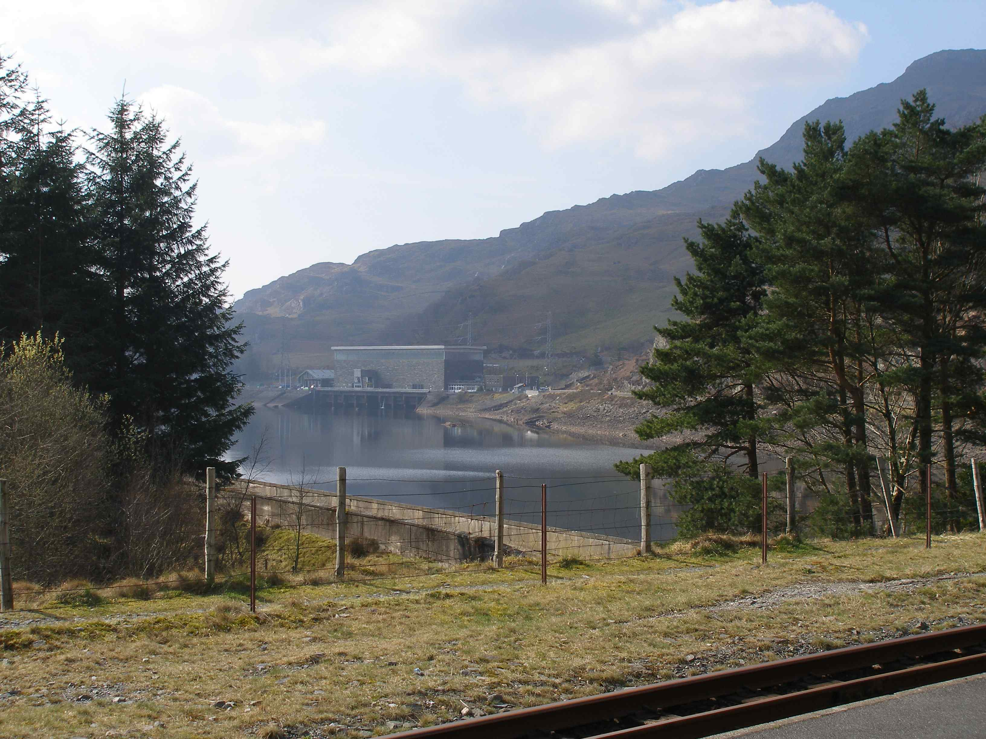 The pumped-hydro electric power station from Tan-y-Grisiau station. The line used to run along the road leading to the power station and then through the actual site - the old cutting on the other side is still visible. The new line now climbs from the station before emerging just below the roof line of the Power Station, level with the upper windows. The ballast bed can just be made out. Commissioned in 1963, Ffestiniog Power Station was the UK's first major pumped storage power facility. Although of an older generation to those at Dinorwig, Ffestiniog's four generating units are still capable of achieving a combined output of 360MW of electricity - enough to supply the entire power needs of North Wales for several hours. The Generation Cycle begins at Llyn Stwlan - Ffestiniog's upper reservoir. Large screens inside the intake towers are opened to activate the high-pressure downflow.