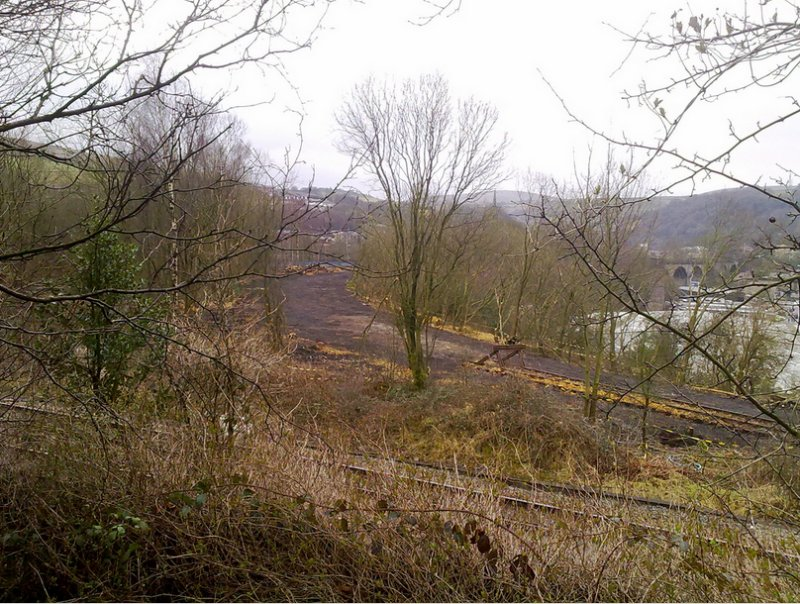 9 March 2012: Andrew Stopford's photograph shows the site of short curve linking the Calder Valley line to the Copy Pit line cleared ready to be re-instated. The Copy Pit line is crossing left to right in the foreground, and the viaduct leading to Todmorden Station, which carries the existing Calder Valley line, is visible centre right. The re-instated line will follow the excavated and cleared dark coloured formation curving towards the viaduct.