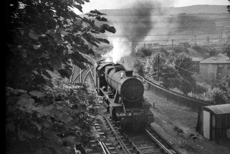 LMS Stanier 8F 2-8-0 48519 of Rose Grove shed heads out of the sun at Stansfield Hall Todmorden to buffer up to a Class 40 diesel-hauled coal train and bank it up to Copy Pit summit on the Burnley line on 1 August 1968, with only two more days to go for the Copy Pit bankers.