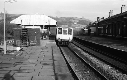 A three-car Class 110 heading for Leeds stands at the eastbound platform 2 at Todmorden railway station, after the canpoy has been removed from platform 1, but the easterly canpoy on platform 2 and the station master's house still stand The class 110 'Calder Valley'unit displays a '0000' headcode.