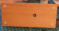 Underside of plinth showing recessed hole and bolt holding Pannier to oak plinth
